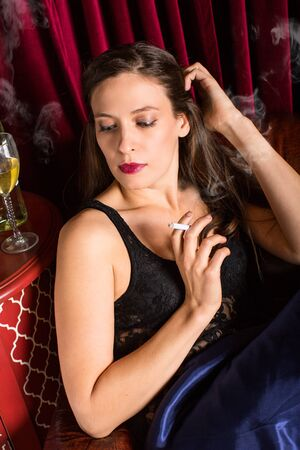 Woman smoking cigarette in a lounge photo