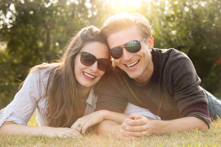Happy young couple wearing sunglasses lying in the grass photo