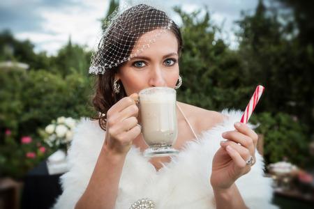 hot chocolate: Novia hermosa bebiendo chocolate caliente y con un palo de menta