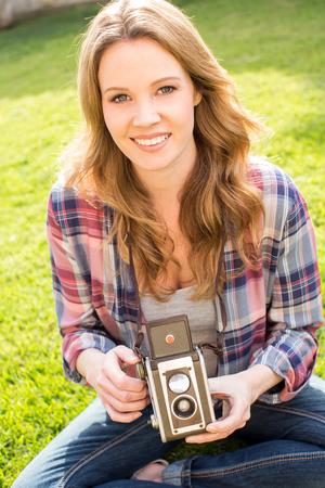amateur: Mujer joven que usa su cámara antigua fuera en el césped
