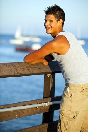 beach hunk: Young man standing on the pier