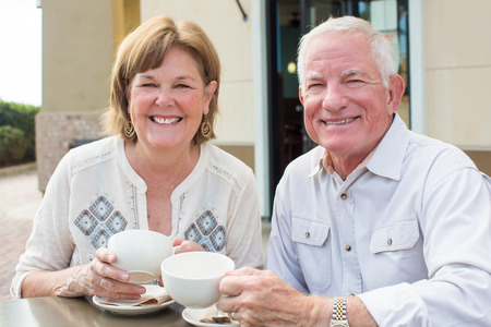Happy mature senior couple reading a newspaper outside at a cafe Stock Photo - 48198932