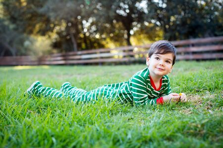boy kid: Cute little boy in christmas pajamas outside in the grass