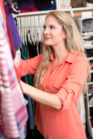 summer dress: Woman looking through clothing in closet