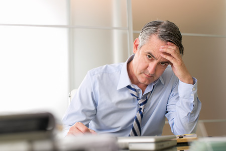 Frustrated stressed business man in an office Standard-Bild