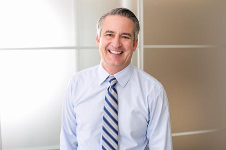 persona pensando: Madura feliz hombre de negocios sonriente en una oficina Foto de archivo