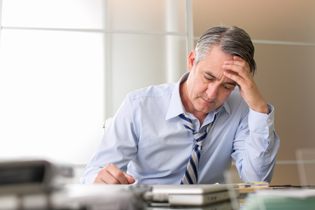 worried businessman: Frustrated stressed business man in an office Stock Photo