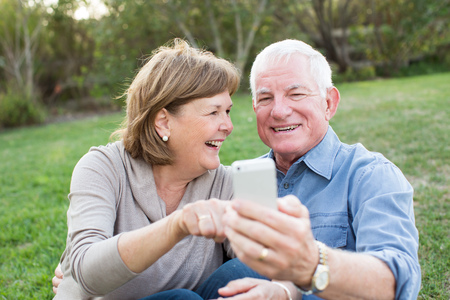 dental health: Happy senior couple taking selfies of eachother outside