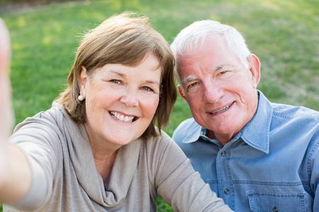 senior women: Happy senior couple taking selfies of eachother outside