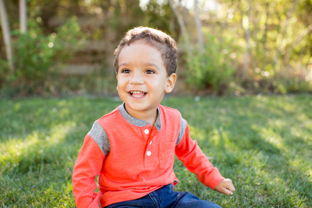 american content: Cute little boy sitting in the grass outside