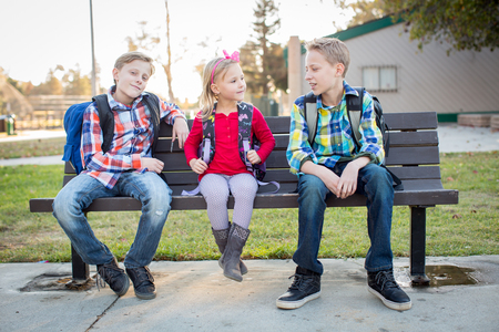 Young school kids sitting on bench