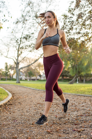 Young ethnic woman running outside