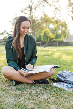 Young ethnic woman outside studying school book