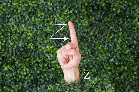 Sign Language Letter Z made with hand against green plant background Banque d'images