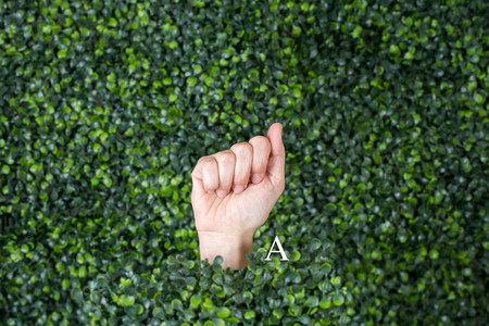 Sign Language Letter A made with hand against green plant background Banque d'images