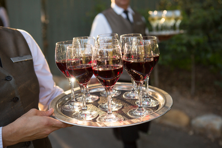 Waiter carrying glasses of red wine on a tray