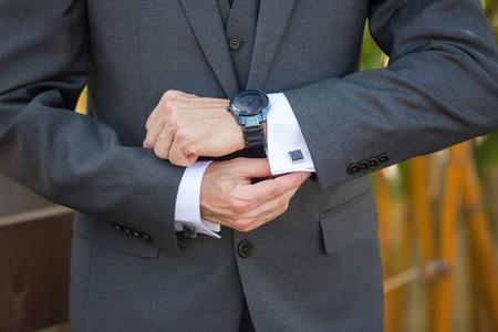 Man adjusting his cufflinks wearing a watch