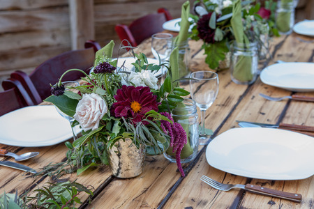 Table scape with dark red florals and wood accents Banque d'images