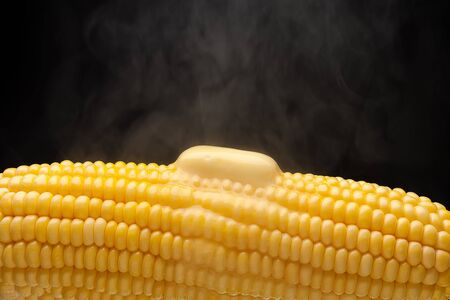 Hot corn with steam and melting butter closeup photo