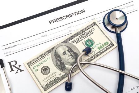 Stethoscope on a prescription with cash for healthcare and medicine photo
