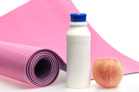 Yoga mat with milk and apple on white background photo