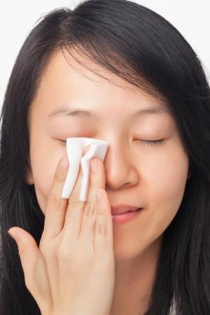 Aziatische jonge vrouw reiniging gezicht met wattenschijfje