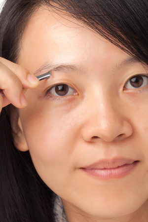 Woman plucking her eyebrows with tweezers photo