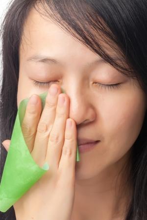 piel rostro: Las mujeres con piel grasa utilizando l�mina de absorci�n de aceite en su cara