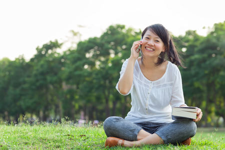 Woman talking on mobile phone and smiling in park photo