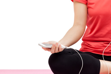 Woman holding smart phone in exercise outfit isolated on white background Stock Photo