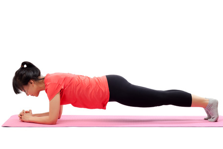 Vrouw doet plank oefening geà ¯ soleerd op witte achtergrond