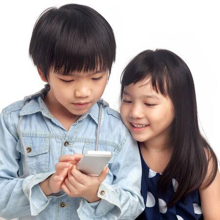 Bambini che giocano su smartphone su sfondo bianco Archivio Fotografico