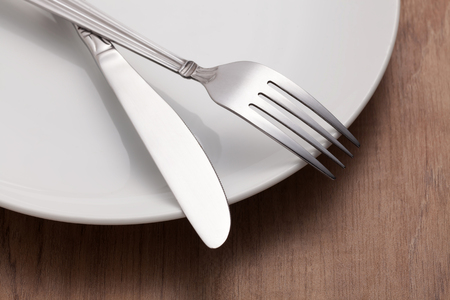 Fork and knife on white plate on wooden table Stock Photo