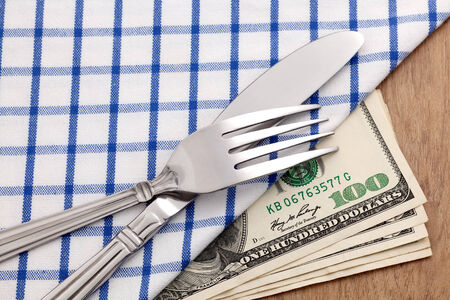 Fork and knife on dollar bills for food business concept photo