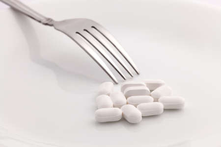 Pills on white plate with fork photo