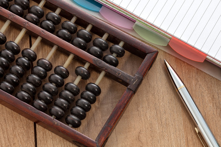 Accounting abacus on wooden table with paper and pen photo