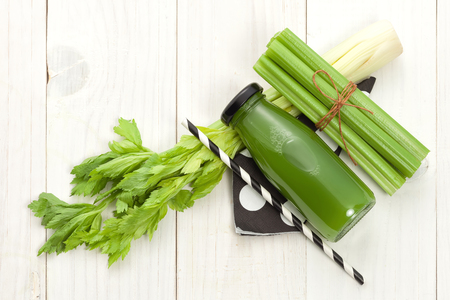 Vegetable juice in bottle with celery stalk on white wood background