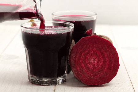 Beetroot with beet juice on white wood