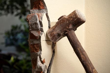 집 리모델링을 위해 망치로 벽을 깨고