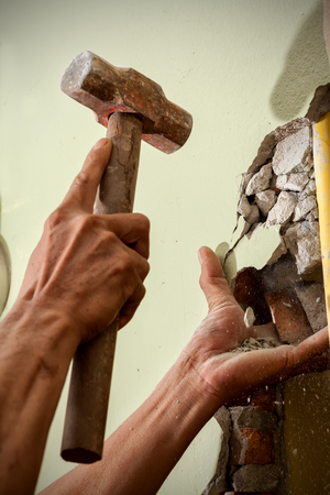 Breaking wall with hammer for renovating house