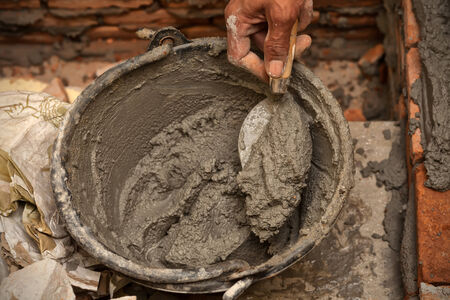 Cement mortar with trowel in worker hand photo