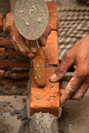 Worker laying brick wall with cement photo