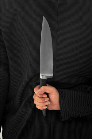 Closeup Businessman Holding Knife Behind His Back conceptual image Isolated photo