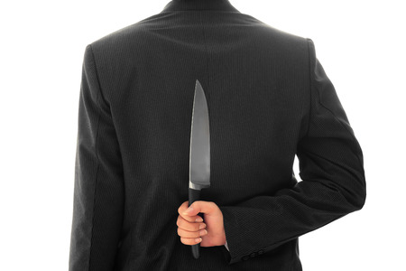 Businessman Holding Knife Behind His Back conceptual image Isolated photo