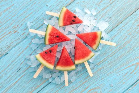 sommer: Wassermelone Eis am Stiel lecker frische Sommer Obst süßen Dessert auf Vintage alten Holz Teakholz blau