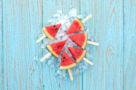 スイカのアイス キャンデーおいしい新鮮な夏フルーツ甘いデザート ヴィンテージの古い木製チーク材の青 写真素材