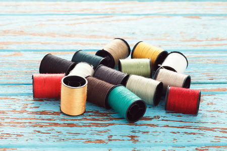 colorful still life: colorful thread needlework embroidery tailor craft repair background blue wood teak still life vintage