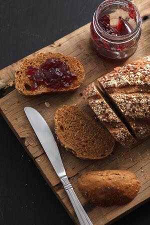 breakfast food: Dark multigrain bread fresh baked rustic breakfast food Whole grain homemade bakery tasty fruit jam berry