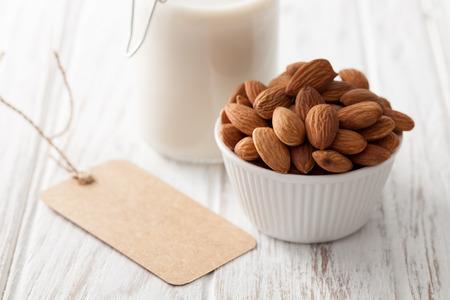 le lait d'amande bio écrou sain végétalien végétarien boisson fond blanc teck bois rustique encore l'étiquette de vie Banque d'images