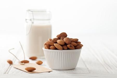 Amandelmelk organische gezonde noot vegan vegetariër drankje witte achtergrond hout teak rustieke nog label life Stockfoto - 51798498